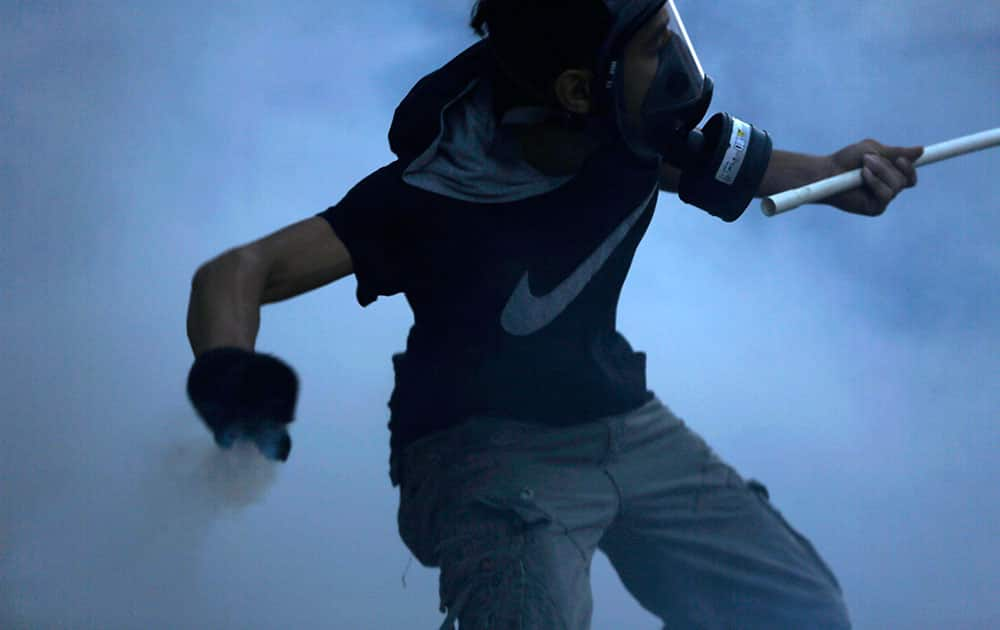 A masked Bahraini anti-government protester carrying a flag holds a tear gas canister he is preparing to throw back toward police who fired it during clashes in Bilad Al Qadeem, Bahrain, a suburb of Manama.