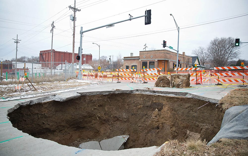 This  photo shows a sinkhole that swallowed up an entire section of a street near downtown Omaha Neb. The sinkhole is about 25 feet in diameter and about 15 deep, officials said. No injuries or property damage was reported.