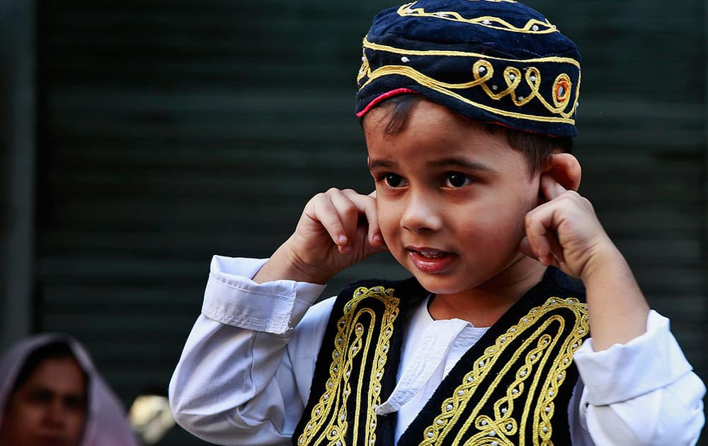 A boy protect his ear from the noise of crackers during a procession of devotees in Mumbai.