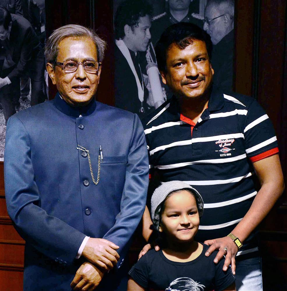 People pose for photographs next to a wax statue of President Pranab Mukherjee at Mothers Wax Museum.