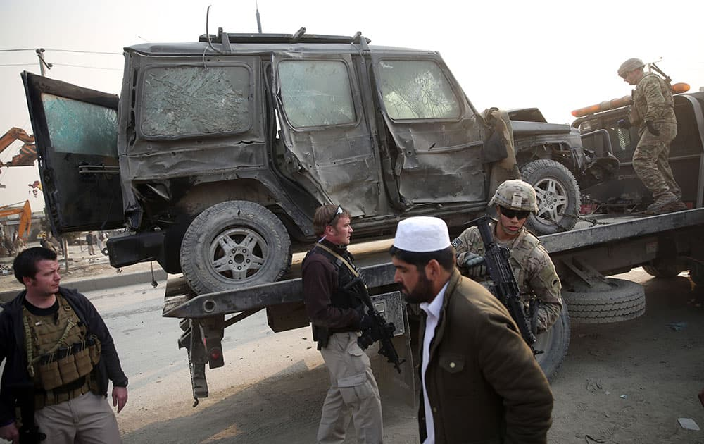 An Afghan man walks past foreign security forces searching a destroyed vehicle at the site of a suicide car bomb attack in Kabul, Afghanistan.