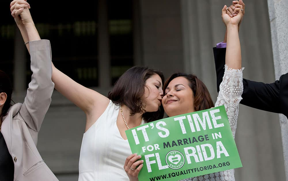 Catherina Pareto and her partner Karla Arguello celebrate on the court house steps after Circuit Court Judge Sarah Zabel lifted a stay on her July ruling that Florida's same sex marriage ban violates equal protections under the U.S. Constitution, in Miami.