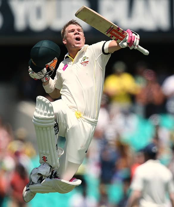 Australia's David Warner jumps to celebrate making 100 runs against India during their cricket test match in Sydney.