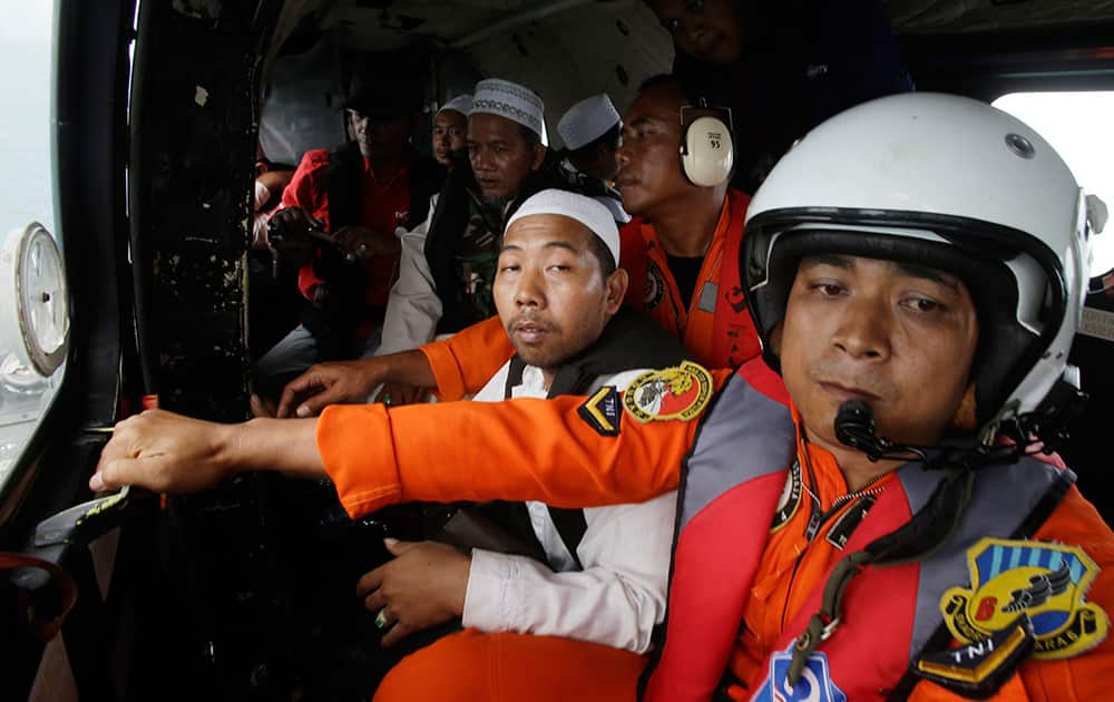 Muslim clerics sit inside an Indonesian Air Force NAS 332 Super Puma helicopter during a flight over the Java Sea off Pangkalan Bun, Central Borneo, Indonesia where the ill-fated jetliner went down to offer prayers for the victims.