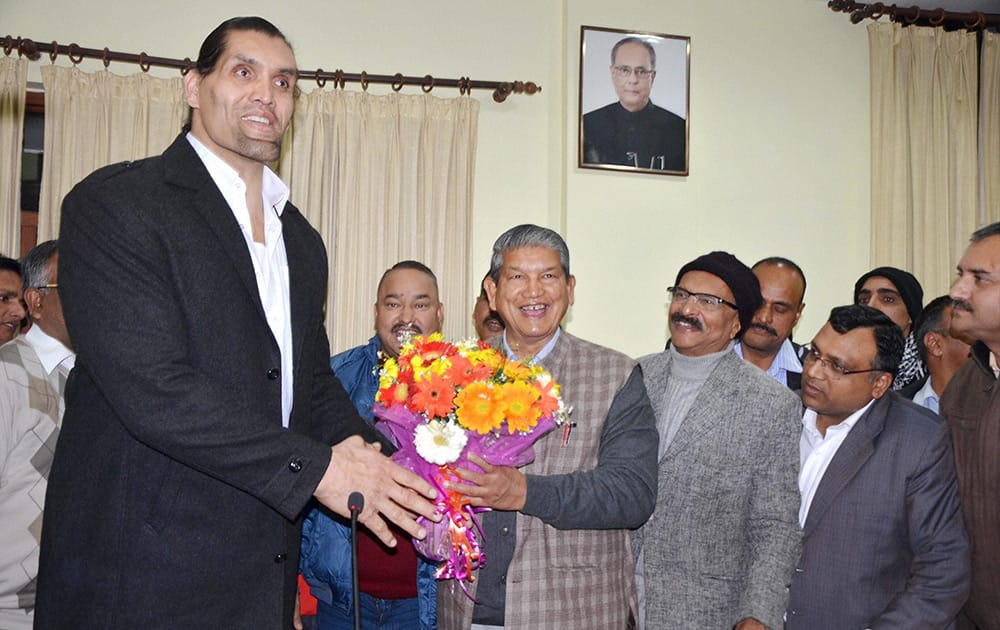 Chief Minister Harish Rawat greets WWE wrestler Khali at the CM residence in Dehradun.