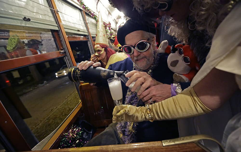 Members of the Phunny Phorty Phellows, pour champagne during their night of revelry aboard a streetcar in New Orleans. King's Day is a tradition marking the 12th night after Christmas and the official start of the Mardi season.