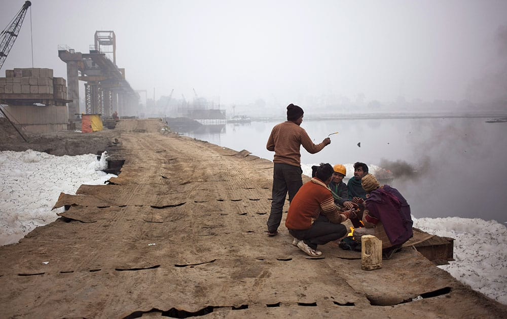 Construction workers sit by a fire to keep themselves warm on the banks of the Yamuna River on a foggy morning in New Delhi, India.