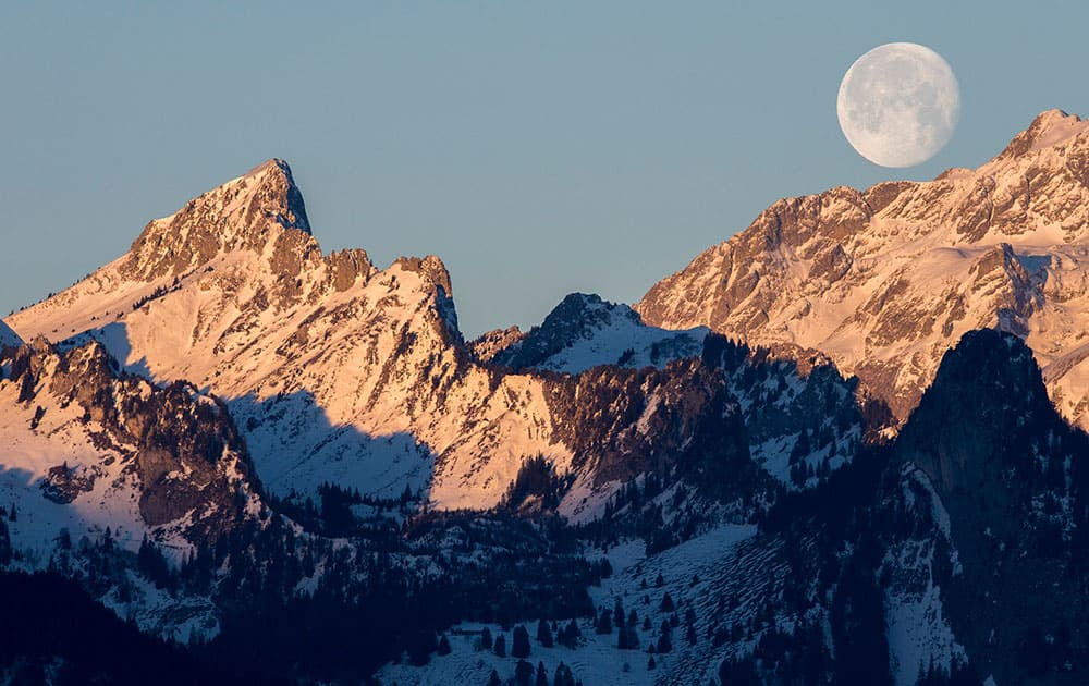The waning moon is setting over the mountain 'Les Cornettes de Bise' located at the border of the Haute-Savoie and the Valais canton of Switzerland in the Chablais Alps, photographed from Glutieres, Switzerland.
