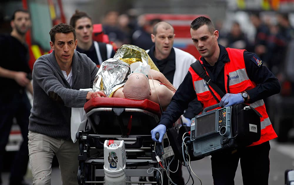 An injured person is evacuated outside the French satirical newspaper Charlie Hebdo's office, in Paris.