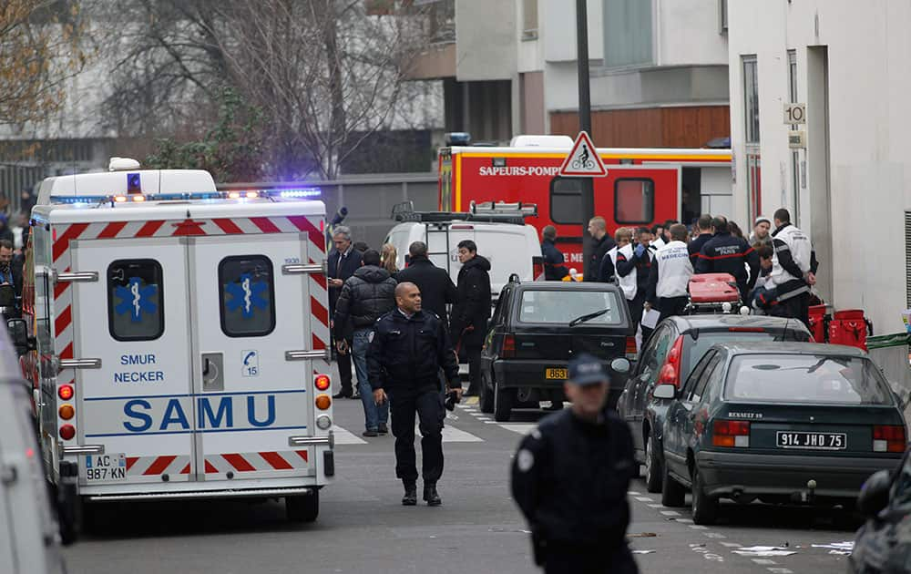 Police officers and firemen gather outside the French satirical newspaper Charlie Hebdo's office, in Paris.