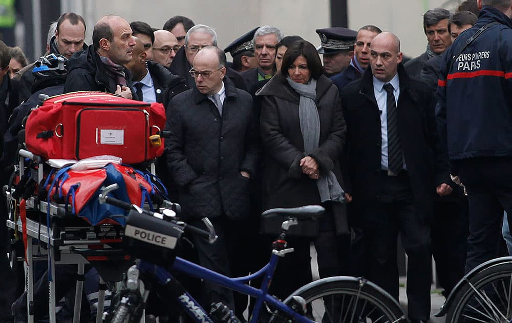 French Interior Minister Bernard Cazeneuve, center left, and Paris' mayor Anne Hidalgo, center right, arrive at the French satirical newspaper Charlie Hebdo's office, in Paris.