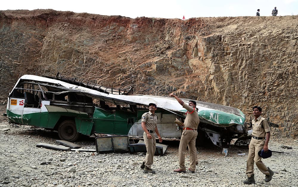 Police officers point at people standing above, as they inspect the wreckage of a bus that fell into a gorge in Penukonda, about 145 kilometers north of Bangalore. The passenger bus veered off a road in southeastern India and fell into the gorge on Wednesday, killing at least 16 people, most of them college and middle school students, police said. More than 50 other people were injured in the accident.
