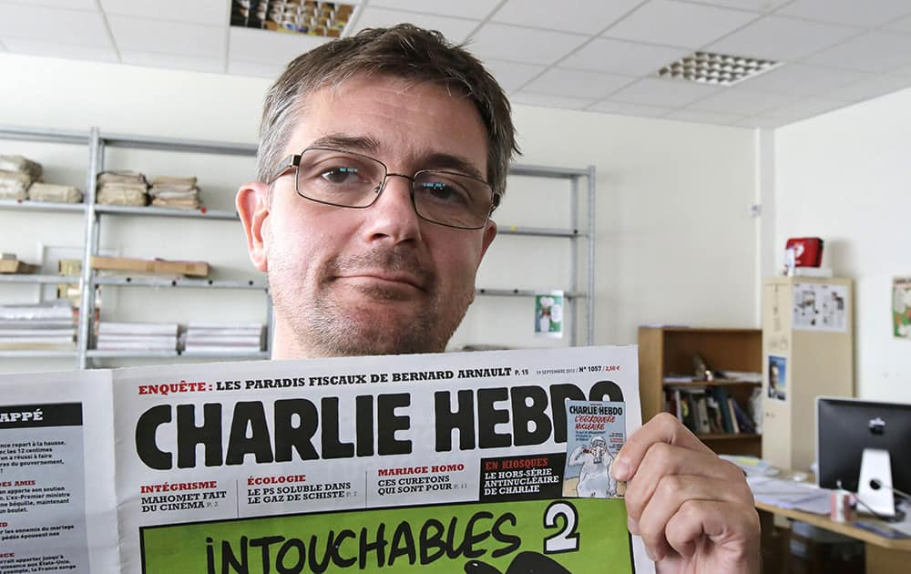 FILE PHOTO, The publishing director of the satyric weekly Charlie Hebdo, displays the front page of the newspaper as he poses for photographers in Paris.