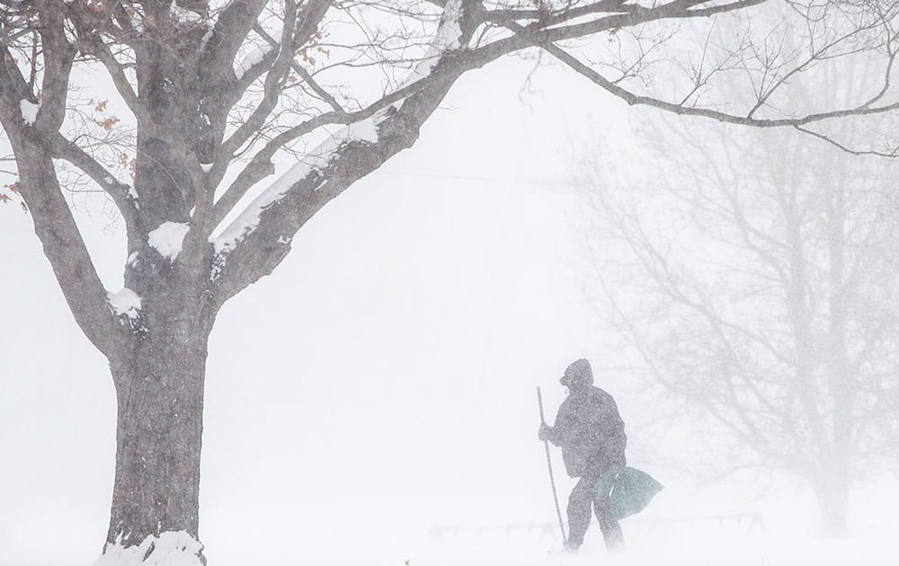 A man walks through snow at Pinhook Park in South Bend, Ind. In Indiana, Indianapolis Public Schools, one of the state's largest school districts, canceled Wednesday's classes, as did many others across the state's northern half, where a daylong wind chill warning was in effect.