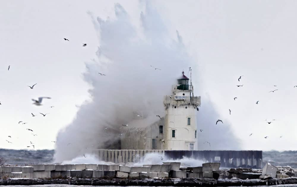 A large wave off Lake Erie engulfs the lighthouse at the entrance to Cleveland harbor.  A blast of arctic air is expected to stick around Ohio a few more days into at least the early part of the weekend and wind chills, already reported below zero in some areas, could dip as low as minus 25 degrees.