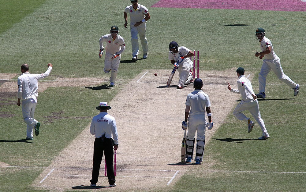 Teammates come running toward Australia's Nathan Lyon, after he bowled out India's Rohit Sharma,  for 53 runs on the third day of their cricket test match in Sydney.