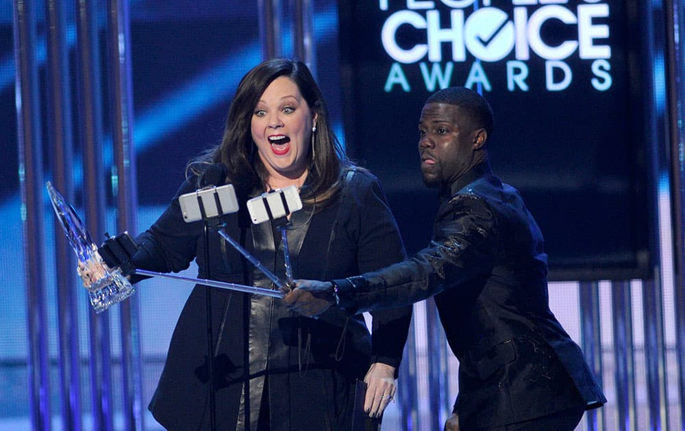 Kevin Hart, right, films Melissa McCarthy as she accepts the award for favorite comedic movie actress at the People's Choice Awards at the Nokia Theatre.