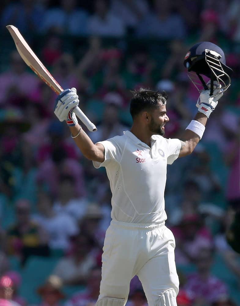India's Virat Kohli raises his bat after making 100 runs against Australia on the third day of their cricket test match in Sydney.