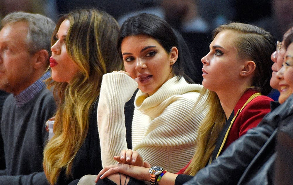 Model Kendall Jenner, sits with her half-sister Khloe Kardashian, as they watch the Los Angeles Lakers play the Los Angeles Clippers during the second half of an NBA basketball game, in Los Angeles.