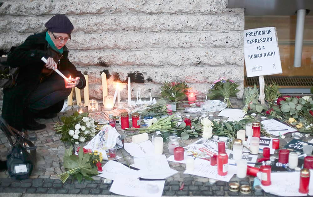 A woman lights candles to commemorate the victims killed in an attack at the Paris offices of the weekly newspaper Charlie Hebdo after masked gunmen stormed their offices, in front of the French Embassy in Berlin.