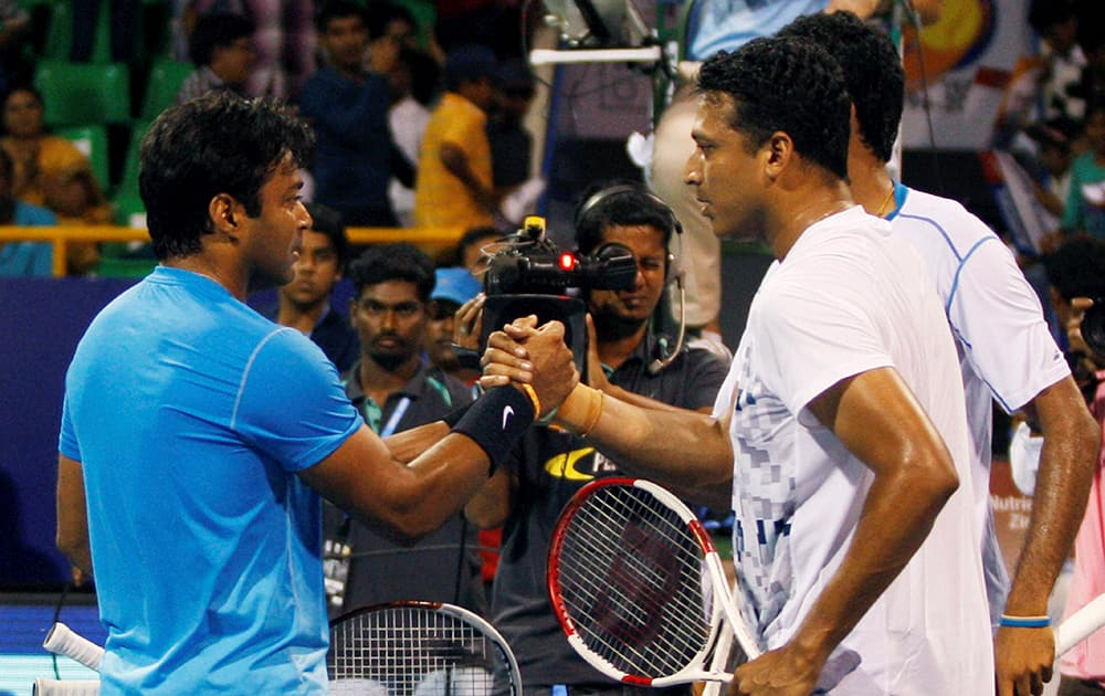 Tennis player Leander Paes and South African tennis player Raven Klaasen shake hands with Indias Mahesh Bhupathi and Saketh Myneni after winning their match at ATP Chennai Open 2015 at SDAT Tennis Stadium in Chennai.