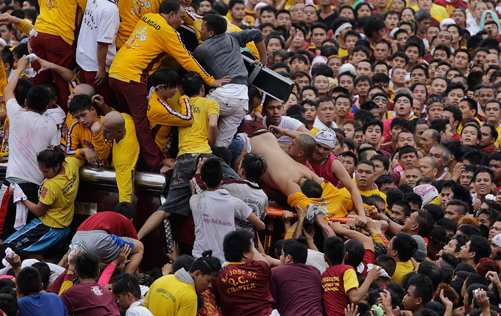 An unconscious devotee is loaded into a stretcher during a raucous procession to celebrate the feast day of the Black Nazarene in Manila, Philippines.