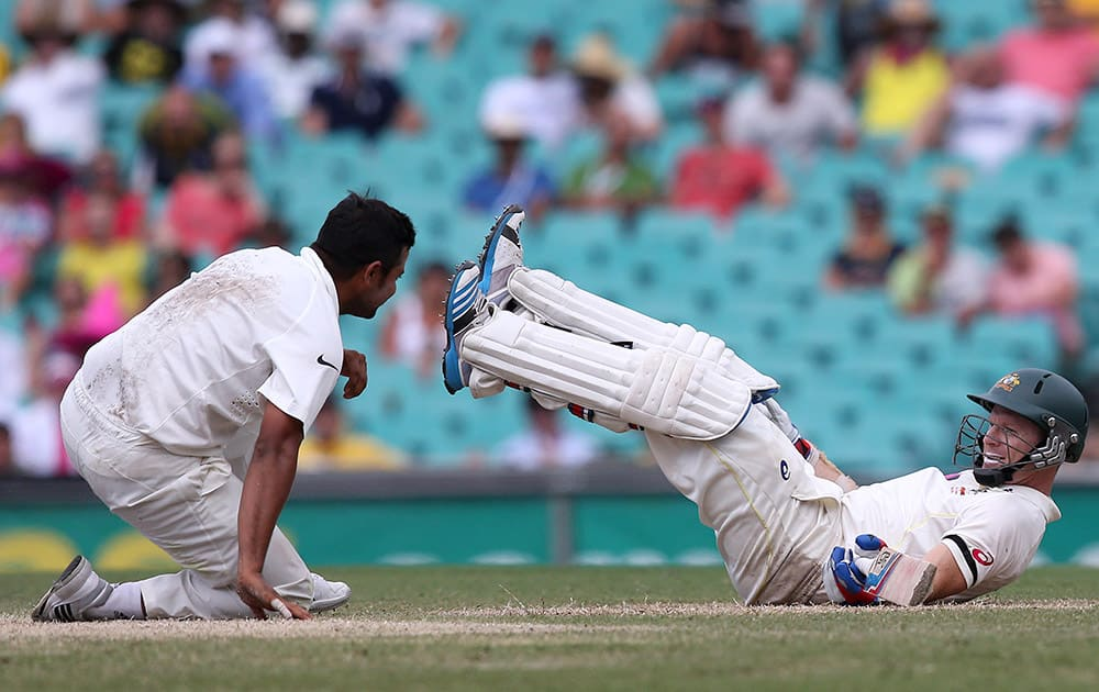 Australia's batsman Chris Rogers, and India's Suresh Raina fall to the ground after colliding on the pitch on the fourth day of their cricket test match in Sydney.