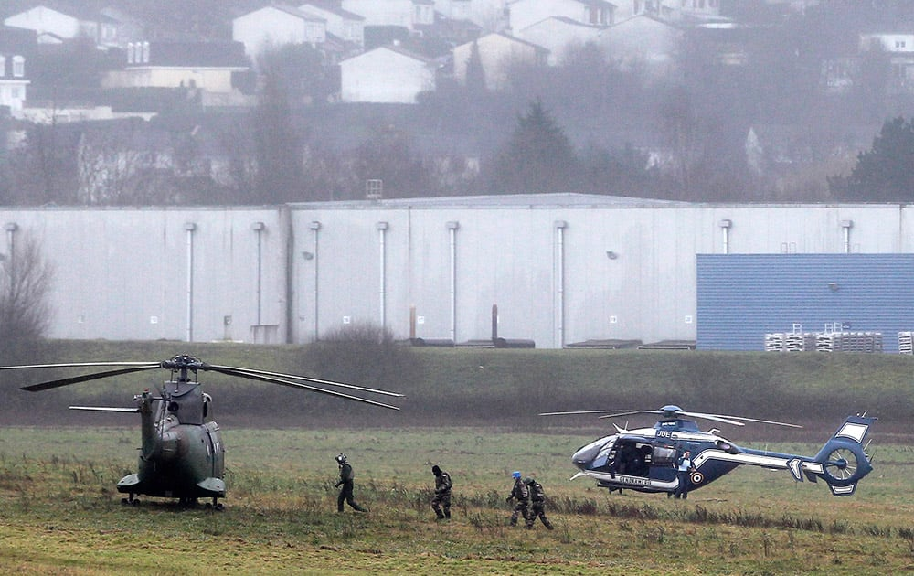 Police and army forces take positions in Dammartin-en-Goele, northeast Paris, as part of an operation to seize two heavily armed suspects. French security forces swarmed a small industrial town northeast of Paris Friday in an operation to capture a pair of heavily armed suspects in the deadly storming of a satirical newspaper.