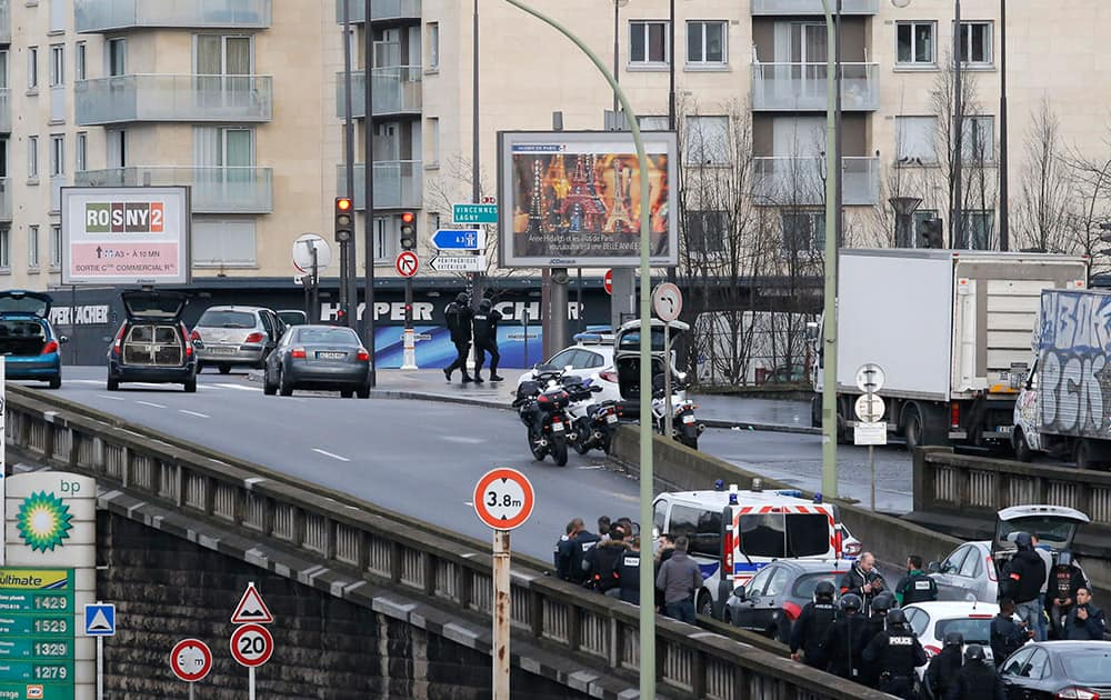 Police officers walk in front of an hostage-taking situation at a kosher market, seen in blue in background, in Paris.