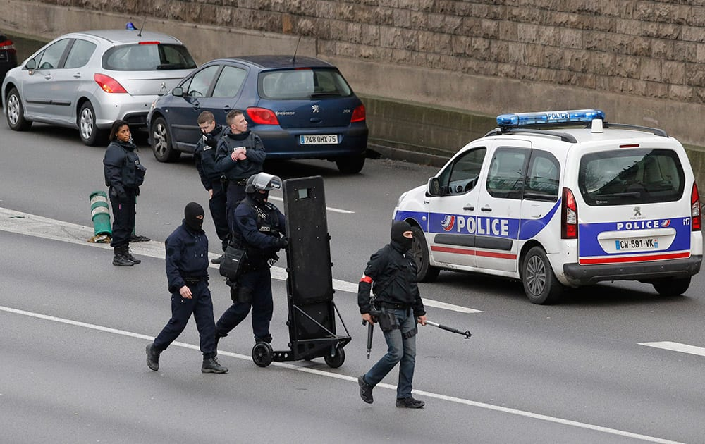 Hooded police officers walk on the closed ring road that circles Paris near a hostage-taking situation at a kosher market in Paris.