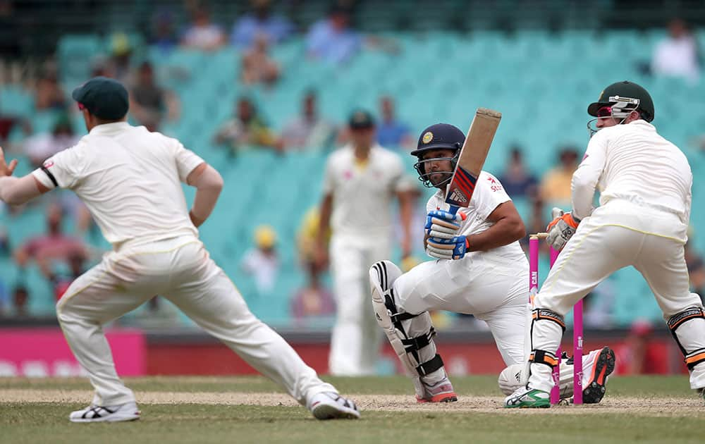 Rohit Sharma sweeps past Australia's Brad Haddin and David Warner, left, on the fifth day of their cricket test match in Sydney.