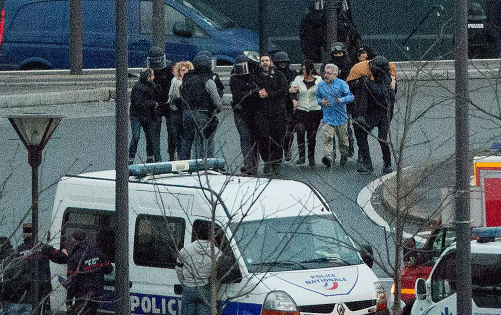Security officers escort released hostages after they stormed a kosher market to end a hostage situation, Paris.