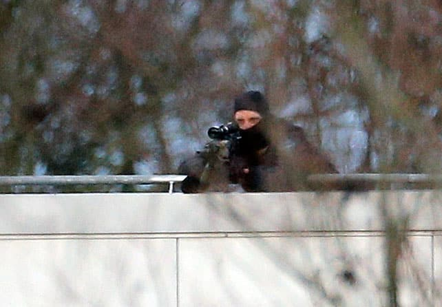A hooded police officer aim from a rooftop in Dammartin-en-Goele, northeast of Paris, where the two brothers suspected in a deadly terror attack were cornered.