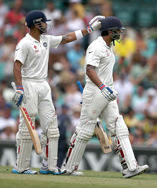 Murali Vijay, gets a pat on his head from his captain Virat Kohli after he was caught behind for 80 runs on the fifth day of their cricket test match in Sydney.