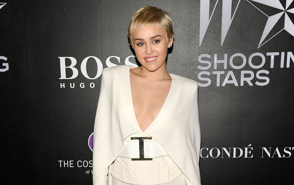 Event co-host Miley Cyrus poses at the opening of W Magazine's 'Shooting Stars' exhibit at the Old May Company Building, in Los Angeles.