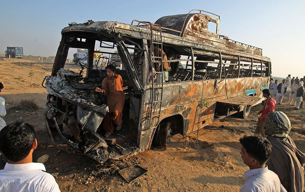 Pakistani gather around and inside the wreckage of a passenger bus that was destroyed after colliding with an oil tanker on a highway about 50 kilometers (31 miles) outside of Karachi, Pakistan.