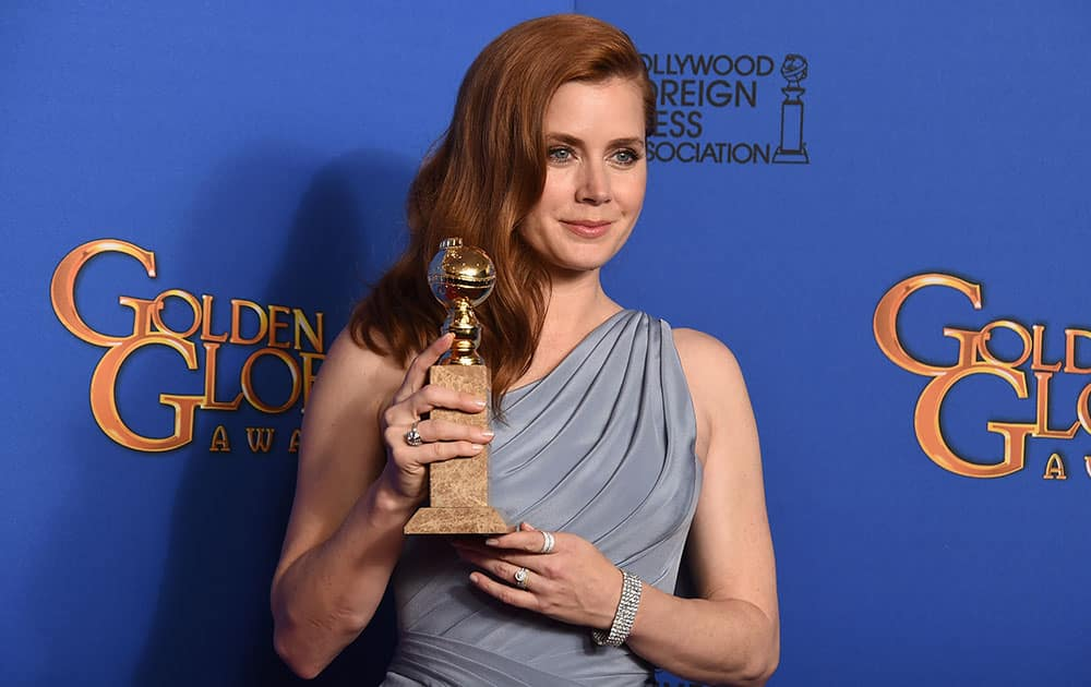 Amy Adams poses in the press room with the award for best actress in a motion picture - musical or comedy for