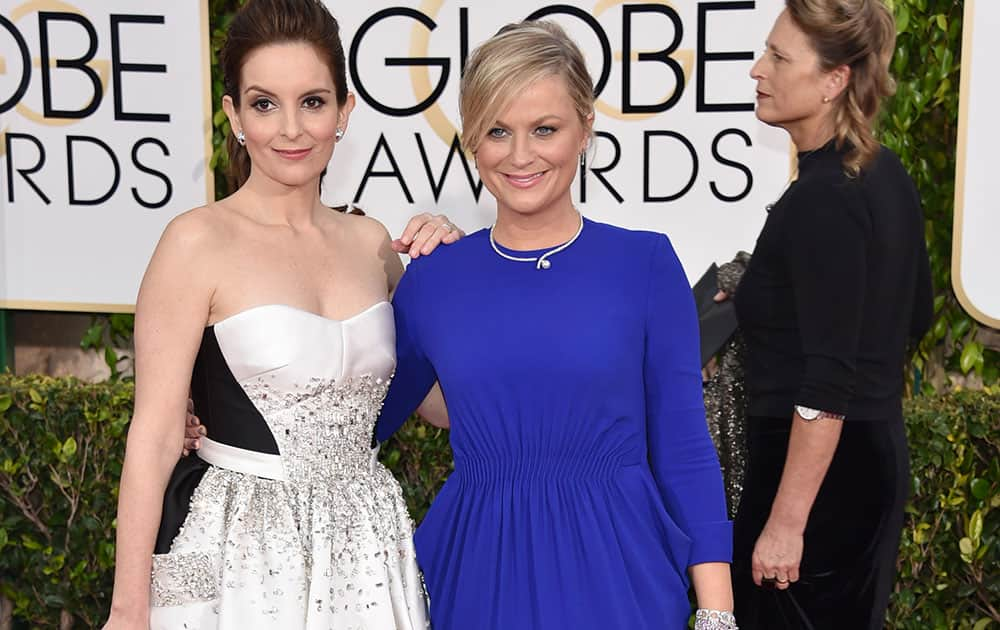 Tina Fey, left, and Amy Poehler arrive at the 72nd annual Golden Globe Awards.