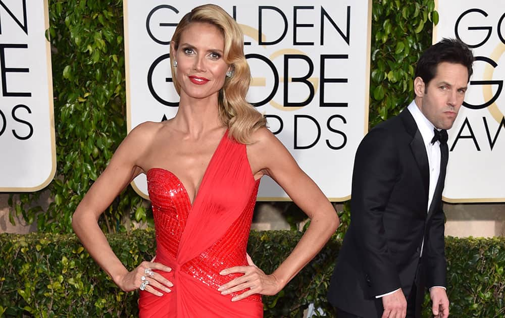 Paul Rudd, right, looks on as Heidi Klum poses at the 72nd annual Golden Globe Awards.