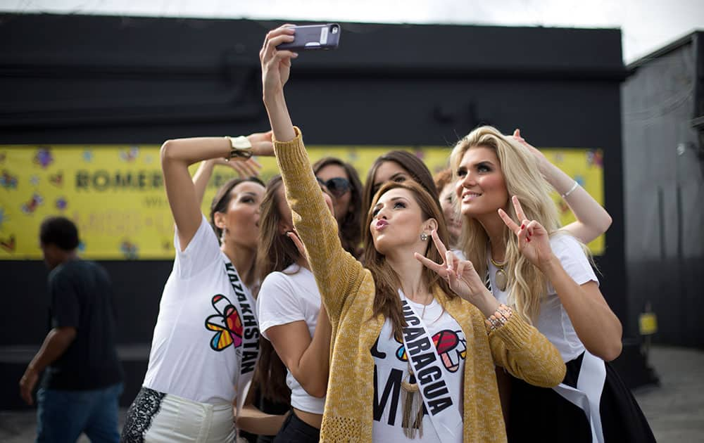 Miss Nicaragua, Marline Barberena, front, takes a selfie with other contestants after they painted on a wall in Miami's Wynwood area.