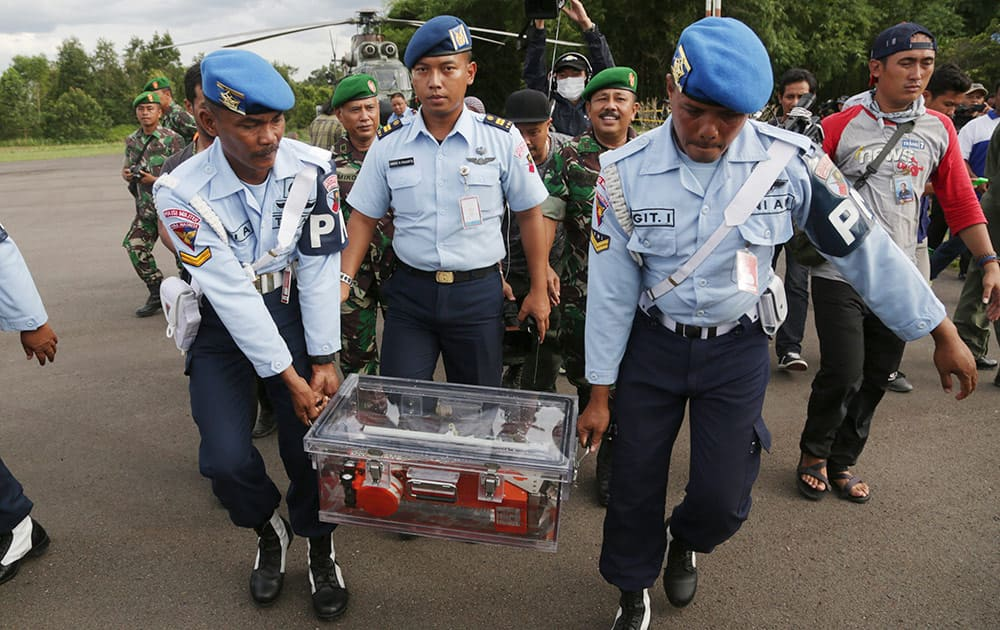 Indonesian air force personnel carry Flight data recorder of the ill-fated AirAsia Flight 8501 that crashed in the Java Sea, at airport in Pangkalan Bun, Indonesia.