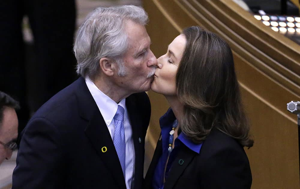 Oregon Gov. John Kitzhaber kisses his fiance, Cylvia Hayes, after being sworn in for an unprecedented fourth term, in Salem, Ore.