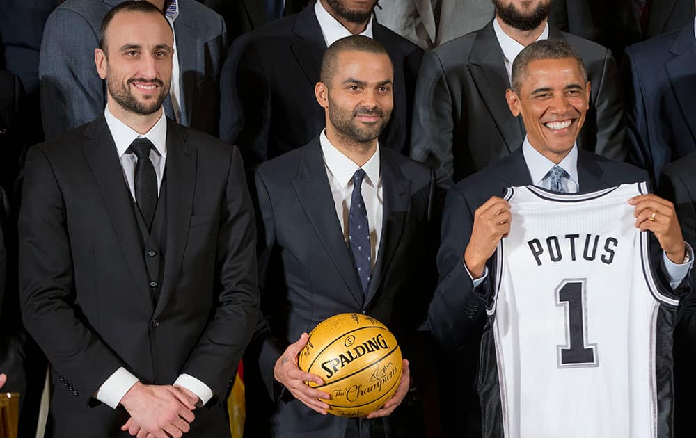 President Barack Obama holds up a San Antonio Spurs team basketball jersey as he honors the 2014 NBA Champions the San Antonio Spurs basketball team during a ceremony in the East Room White House in Washington.