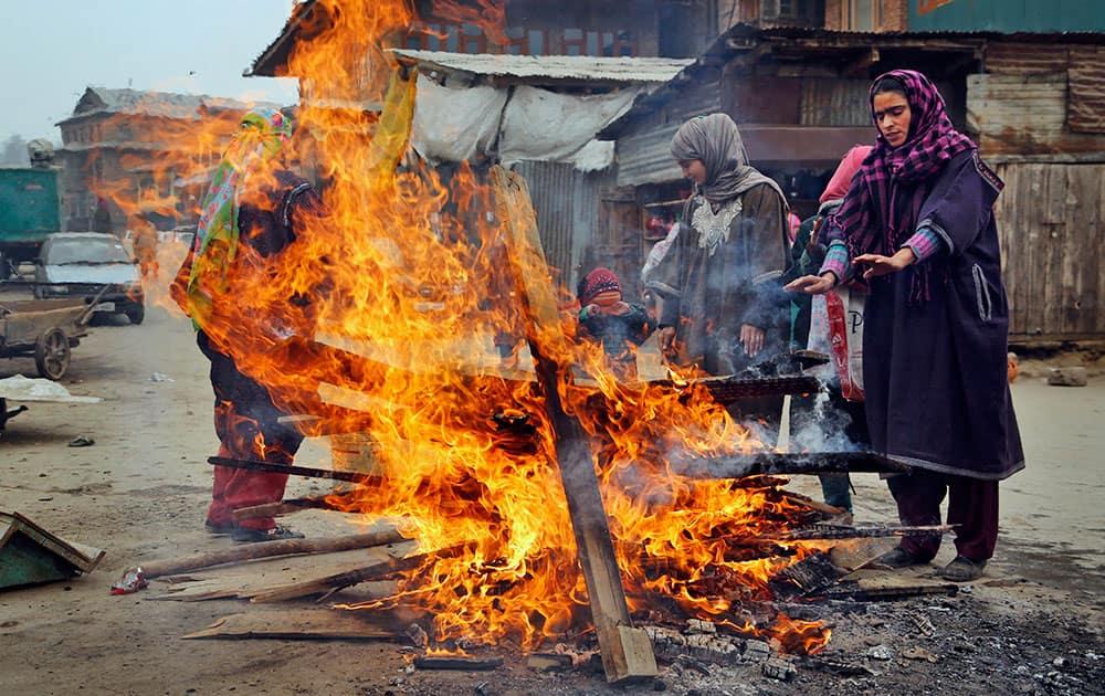 Kashmiri women warm their hands near a fire on a cold day in Srinagar.
