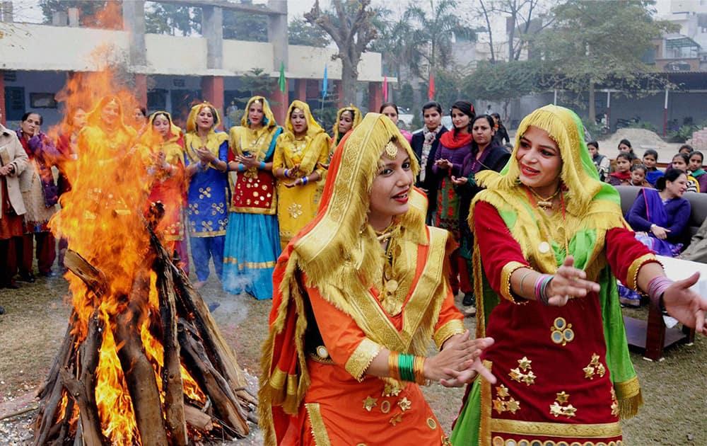 Attired in traditional dress, college girls perform gidha (popular folk dance of women in Punjab) around a bonfire as they celebrate Lohri Festival.
