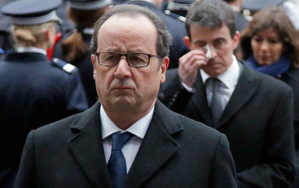 French President Francois Hollande, followed by Prime Minister Manuel Valls, march during a ceremony to pay tribute to the three police officers killed in the attacks, in Paris, France.