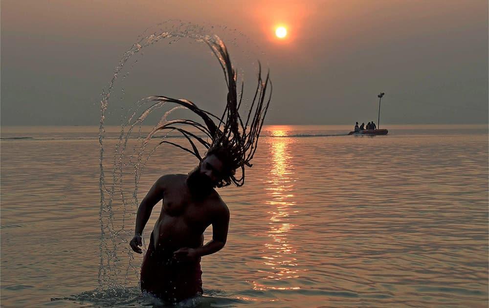 A sadhu splashes water from his jatta (hair-locks) while taking a holy dip in the river Ganga, ahead of Makar Sankranti at Sagar Island.