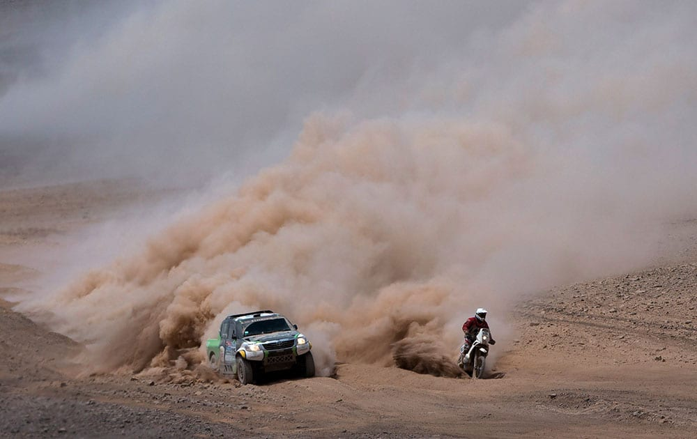 Toyota driver Yazeed Alrajhi, from Saudi Arabia, and co-pilot Timo Gottschalk, from Germany, left, overtake KTM motorcyclist Damien Udry, from Switzerland, during the ninth stage of the Dakar Rally between the cities of Iquique and Calama, Chile.