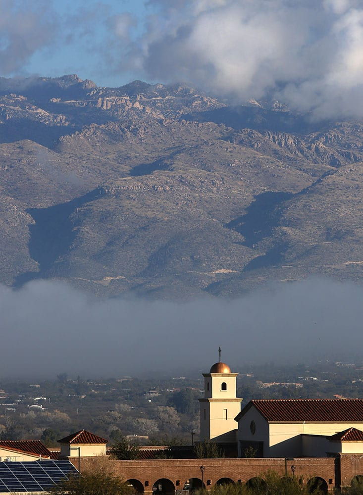 Heavy fog moves along the bottom of the Tucson valley as it partially lifts revealing parts of the Santa Catalina Mountains and the Corpus Christi Catholic Church in Tucson, Ariz.