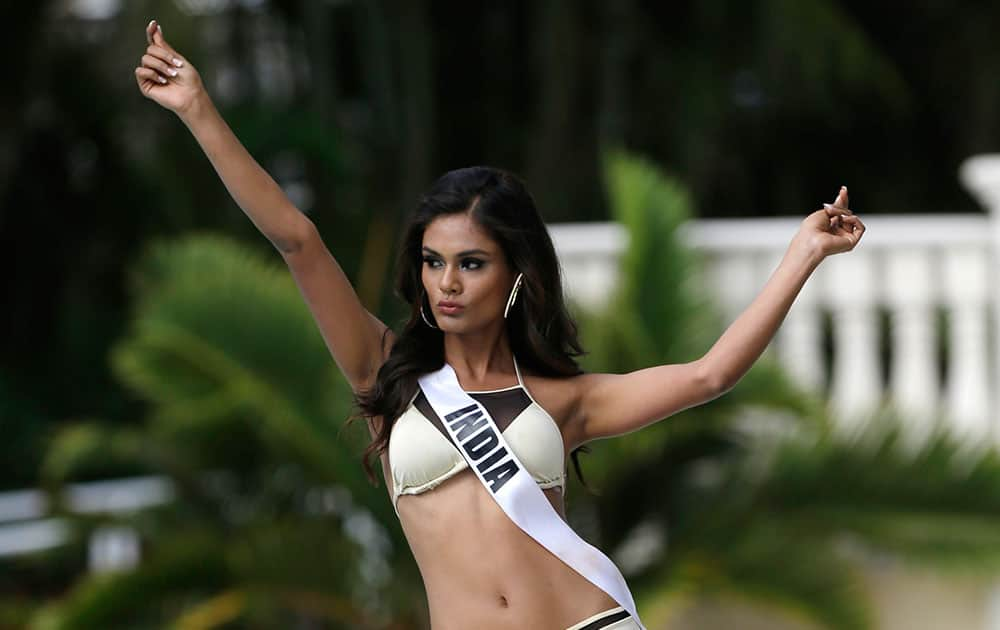 Miss Universe contestant Noyonita Lodh, of India, walks along the pool during the Yamamay swimsuit runway show.